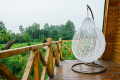 Hanging seat on balcony of wooden cabin Royalty Free Stock Photography