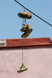 Hanging shoes. Two pairs of sport shoes hanging from a above Royalty Free Stock Photo