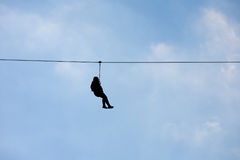 Hanging silhouette of a man on a wire. (Canopy extreme sport Royalty Free Stock Images