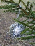 Hanging silver Christmas decoration on fir tree stock images