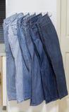 Hanging six jean on hook. Stock Photo