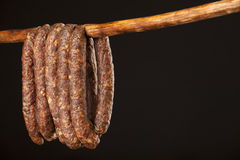 Hanging smoked domestic traditional sausage. On a stick on black background Royalty Free Stock Photography