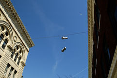 Hanging Sneakers. A pair of sneakers hanging on a wire strung between two buildings royalty free stock photos