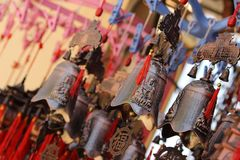 Tibetan Feng Shui decor. Hanging spiritual bells. Made with red, brown thread royalty free stock photo
