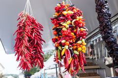 Hanging strands of mixed colorful chili peppers for sale at Sineu market, Majorca Stock Photography