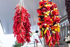 Hanging strings of mixed hot chili peppers for sale at Sineu market, Majorca. Spain Stock Images