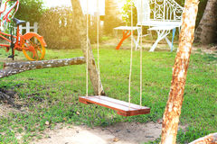Hanging swing bench seat chair on the green grass field Stock Photography