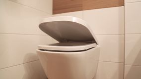Hanging toilet with soft closing toilet seat lid hinge. stock video