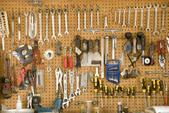 Hanging Tools. Many well-organized & well-used tools hang on a peg board in a garage Royalty Free Stock Images