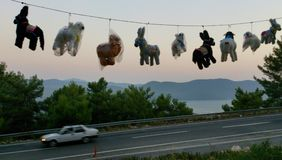 Hanging toys. Many donkey toys hanging on the rope near the road with mountains on background Royalty Free Stock Photos