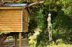 Hanging from a tree. A (toy) skeleton hanging from a tree next to a childrens tree house Stock Image