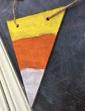 Hanging triangular wood piece with three colors. Stock Image