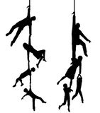 Hanging on. Two editable vector silhouettes of a family hanging at the end of a rope with each figure as a separate object Stock Photos