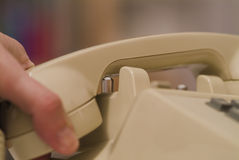 Hanging up the phone. Close up of a person hanging up an older biege phone Stock Photo