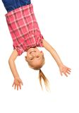 Hanging upside down. Happy laughing 4 years old girl hanging upside down isolated on white with smile on her face Royalty Free Stock Image