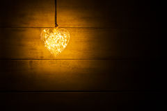 Hanging warm glowing orange heart. On a wooden background stock images