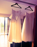 Hanging wedding gown in beautiful morning light. Beautiful two-piece wedding goun hanging from ceiling bahts with morning sunlight coming through balcony's door royalty free stock photography