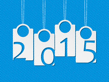 Hanging white labels showing year 2015. On striped blue background Royalty Free Stock Images