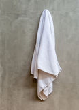Hanging white towel draped on exposed concrete wall in the bathr Royalty Free Stock Photos