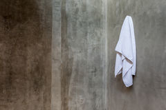 Hanging white towel draped on exposed concrete wall in the bathr Stock Photography