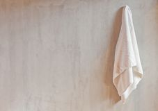 Hanging White Towel. Draped on Exposed Concrete Wall in the Bathroom Stock Photos