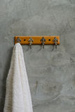 Hanging White Towel draped on Exposed Concrete Wall Stock Image