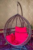 Hanging Wicker Chair. A hanging wicker basket type chair with red cushions against an antique red wood fence Stock Image
