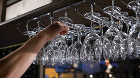 Hanging wineglasses, selective focus, color reflections stock footage