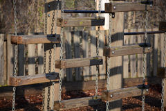 Hanging wooden bars in a playground at a park. Wooden bars for climbing are liked together by chains for children to play on Stock Image