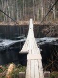 Hanging wooden bridge over a river Stock Photos