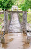 Hanging wooden bridge over the stream Royalty Free Stock Photo