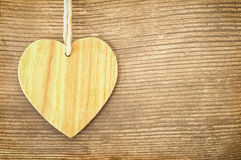 Hanging wooden heart on a wooden background. Country style - greeting card royalty free stock images