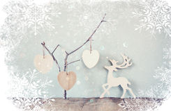 Hanging wooden hearts over and wooden rain deer decoration over wooden background. retro filtered image with snowflake overlay Royalty Free Stock Photo