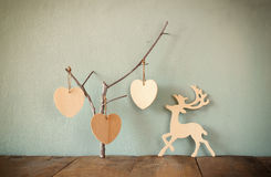 Hanging wooden hearts overand wooden raindeer decoration over wooden background. retro filtered image Royalty Free Stock Photography