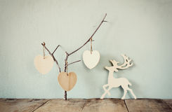 Hanging wooden hearts overand wooden raindeer decoration over wooden background. retro filtered image Royalty Free Stock Image