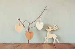 Hanging wooden hearts overand wooden raindeer decoration over wooden background. retro filtered image Stock Image