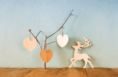 Hanging wooden hearts overand wooden raindeer decoration over wooden background. retro filtered image Stock Photo