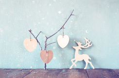 Hanging wooden hearts overand wooden raindeer decoration over wooden background. retro filtered image Stock Images