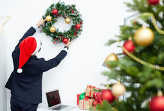 Hanging wreath on wall. Back view of businessman in Santa cap and formal suit hanging xmas wreath on wall of office Stock Photos