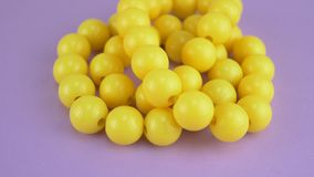 Hanging yellow beads necklaces. Yellow beads necklaces on violet or purple background for female person stock video