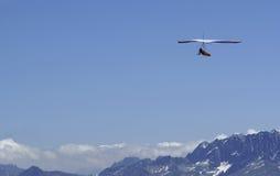 Hanglider. Soars above Pennine Alps in Switzerland Royalty Free Stock Photo