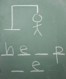 Hangman Help. The game hangman on a blackboard with the words help me almost spelled out as hangman hangs Stock Photography