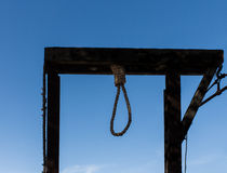 Hangman`s gallows with rope noose against blue sky Stock Photo