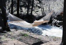 Hangmat die dichtbij rivier wordt gehangen Royalty-vrije Stock Foto's