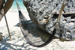 Hangmat het hangen met boom in schaduw bij kust zandig strand Stock Fotografie