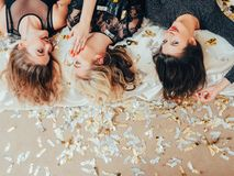 Hangout party females chitchat gossip confetti. It is our secret. Party women chitchat. Hangout females lying upe down swapping gossip. Scattered confetti around stock photo