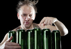Hangover.The drunk man and is a lot of empty beer cans Royalty Free Stock Photo