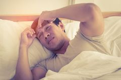 Hangover man on bed woke up with headache royalty free stock image