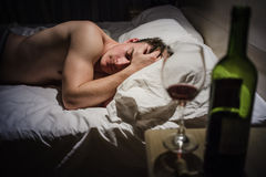 Hangover Man with Headaches in a Bed at Night Royalty Free Stock Images