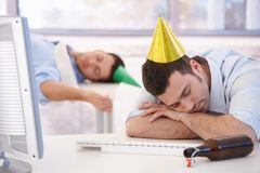 Hangover after office party. Young businessmen sleeping in office after party night Royalty Free Stock Photography